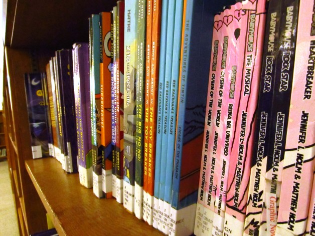Children's graphic novels organized neatly on a library shelf.